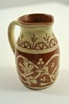 Jug White slip floral design - pale honey glaze Dimensions: H 11cm x W 10.5cm  Notes: Base inscribed 'K Ireland decorated this jug . . '  www.burtonartgallery.co.uk