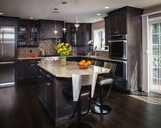 Dark colored cabinets in kitchen with light countertop. See more in our kitchen cabinet gallery.
