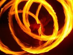 Me, silhouetted laughing in the flames of my poi.