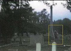 """These photos were taken in a cemetery in Apex, North Carolina. The first shows my husband in the foreground..notice the tall monument in the background. The second photo (taken just seconds later) shows a figure standing next to the tall monument..to the best of my knowledge there was no one else present in the cemetery that evening. If you zoom in on the photo you can make out it's facial features..it appears to be wearing a robe of some kind."