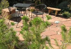 An informal rustic style flagstone patio with some fieldstones randomly placed in the large gaps.