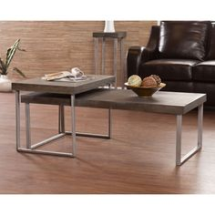 This nesting coffee table set features a burnt oak finish with a weathered gray look. Both tables are supported by metal, silver powder coat U-shaped table legs. Whether stacked together or spaced apart, this table set will enhance your living room!