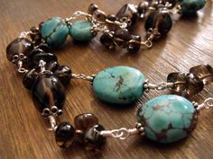 Southwest Drama Long Gemstone Necklace~ This Southwestern sensation is adorned with smoky quartz and blue turquoise gemstone nuggets. Each stone is captured between sterling silver accents. Hand-wrapped with sterling silver wire, they add up to a generous length of thirty-six inches.