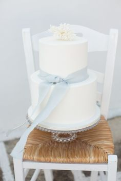 Simple white wedding cake with blue ribbon