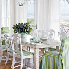 The 10-foot-long heart-pine dining table was painted and distressed; a hodgepodge of side chairs scored at a local thrift store complement the table. A fresh application of candy-stripe fabric unifies the mismatched set of chairs.
