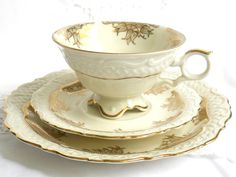 A lovely trio set of cup, saucer and plate with a decoration of gold, richly embossed, on off white porcelain. It was made in Germany by  Oscar Schaller & Co. Nachfolger, between 1935 and 1950. The set is in very good condition, no chips or cracks. 882  Please do not put it in the dishwasher!  For more vintage items please visit our shop: http://www.minoucbrocante.etsy.com  For combined shipping please contact us. We also combine shipping with our other Etsy shop where we sell shabby chic…