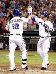 Texas Rangers Mitch Moreland (18) is congratulated for his two run homer by teammate Mike Napoli at home plate in the fourth inning of a baseball game against the Seattle Mariners Monday, April 9, 2012 in Arlington, Texas. (AP Photo/Tony Gutierrez) game 4