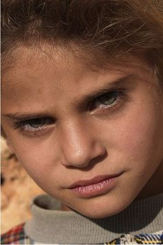 """Syria. Girl from a tribe who lives in a """"dead city"""" near Aleppo. Everyone in the family is blonde with green or blue eyes."""