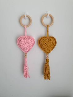 """Hanging heart decoration handmade using 100% cotton. This heart decoration is handmade in your choice of colour. With plenty of colour options you could choose your colour to coordinate with any room in your home, from a nursery, living room to your hallway. The heart itself is crocheted with a 2d effect and is stuffed with non   hypoallergenic stuffing. The heart is hung from a 5cm wooden ring and finished with some wooden beads and a 13cm (5"""") tassel. The full length of the heart hanging…"""