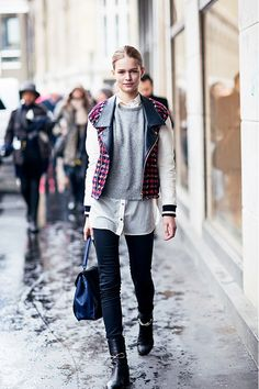 A button-down shirt is paired with a gray sweater, tweed motorcycle jacket, skinny jeans, black Balenciaga boots, and a top-handle bag