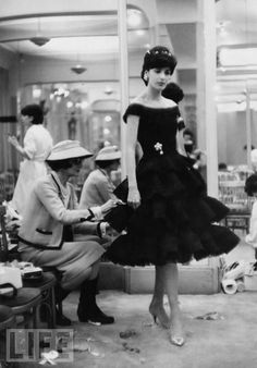 "Another milestone in Chanel's career: Her 1926 debut of ""the little black dress"" in American Vogue — a simple, calf-length frock that the magazine would call ""a sort of uniform for all women of taste."" Pictured: Coco works on an elevated version of the ""LBD"" at her Paris fashion house in 1959. By that time, Chanel was in the midst of a comeback, after temporarily shutting down her business during World War II."
