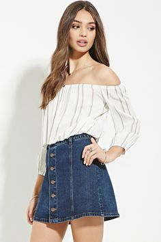 A woven crop top with off-the-shoulder 3/4 sleeves, an elasticized neckline, an elasticized hem, and chevron stripes.
