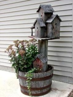 half a wine barrel with a post of bird houses and perennials