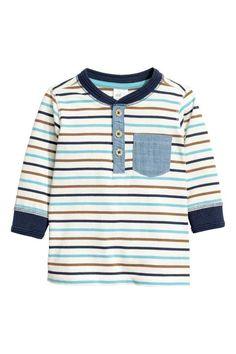 Koszulka henley: Koszulka henley z miękkiego, bawełnianego dżerseju w prążki. Długi rękaw, guziki u góry, kieszonka na piersi. Ściągacz wokół szyi i rękawów.