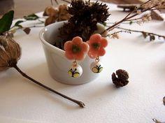 花と蝶のピアスです。【素材】土台:フェルト+樹脂コーティング   ぶら下がっているのはコットンパールです。   (手書きで蝶のイラストを描いた後、樹脂でコーテ...|ハンドメイド、手作り、手仕事品の通販・販売・購入ならCreema。