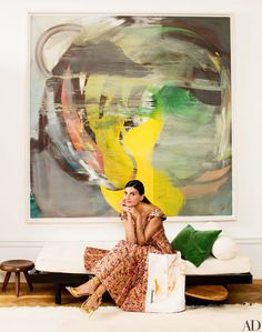 Battaglia-Engelbert sits on a Jean Prouvé daybed beneath the living room's Albert Oehlen painting   archdigest.com