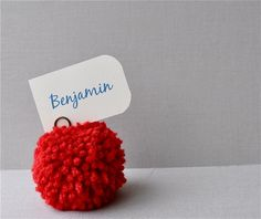 Red yarn pom pom used as place settings for a wedding, birthday, baby shower or other party.  #weddingdecorations #weddingdecor #partyfavor #pompoms