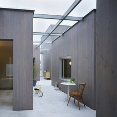 """House in Buzen by Suppose Design Office: """"separate structures are connected under a glass canopy..the wood-clad residence features courtyards and corridors"""""""