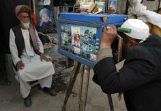 An Afghan street photographer, right, takes a portrait of a customer with a wooden-made camera in Kabul