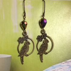 PARAKEET EARRINGS  #3 TPSFB RETAIL These Earrings feature Antique Brass Parakeets on a flowered hoop with Swarovski Purple/Gold Aurora Borealis drops. Antique Brass hooks.  Fast Shipper  Top 10% Seller  Discount on Bundles  Free Gift For All Orders 20 & Up  Smoke Free/Animal Free Home  PayPal  Trades Fireglow Gem Jewelry Earrings