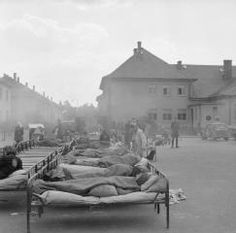 """THE LIBERATION OF BERGEN-BELSEN CONCENTRATION CAMP, APRIL 1945 part of """"WAR OFFICE SECOND WORLD WAR OFFICIAL COLLECTION"""" (photographs) Made by: No 5 Army Film & Photographic Unit Sick patients lie in beds on the Parade Ground at Camp No 2, Hohne Military Barracks, until space can be found for them indoors."""