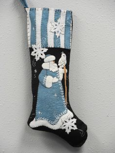 "CD75 Blue Santa ,,  25"" long  applique stocking , heirloom quality .A new color coat and topper on a vintage favorite ! We have both patterns and kits and the kits include the pattern . The kits include wool felts that are washed and ready to use and felted very nicely to add that dimensional look ."