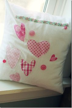 Cute Pillow! Child drew hearts and arranged them on pillow with ribbon and buttons, Mom sewed it up for her. Sweet little project to do with little ones.
