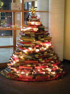 sapin de Noël original réalisé avec des livres empilés et guirlandes lumineuses