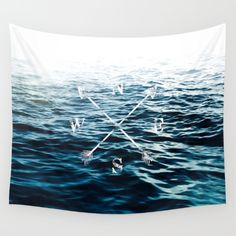 A landscape/ seascape photograph of a blue sea close to the surface waves, fading in to a soft white tone. And above it a symbol of the winds (north, south, east and west) with hand drawn crossed arrows. An image that inspire both calmness and relaxation as adventure and traveling.<br/> <br/> Picture taken in Costa Rica and processed in Lightroom and typography added in Photoshop.<br/> <br/> Additional tags;<br/> ocean, typography, nsew, arrow, serene, zen, relax, summer, travel, holiday