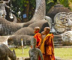 It was a Buddhist Holiday and these three young monks were visiting the Buddha Park, on the Mekong River outside of Vientiane, Laos with there teacher.    The park has over 200 statues.