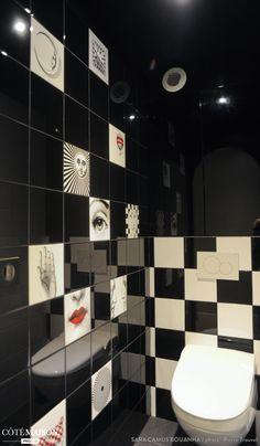 Dans ces toilettes, WC suspendu avec carrelage noir et blanc...