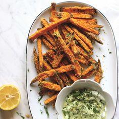 Voor de frieten:  1. Boen de zoete aardappels goed schoon onder stromend water. Snijd ze in lange frieten van 1 cm dik. Leg ze in een kom water, roer even goed en laat ze dan uitlekken (met deze stap verwijder je wat van het zetmeel). Leg ze op een...