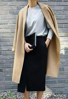 Black pencil skirt with a front slit, grey top with long sleeves, camel coat and black clutch.