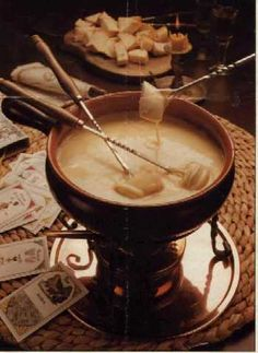 Fondue - Swiss dish prepared by melting cheese with wine in a chafing dish and using long-handled forks to dip cubes of bread into the cheese mixture