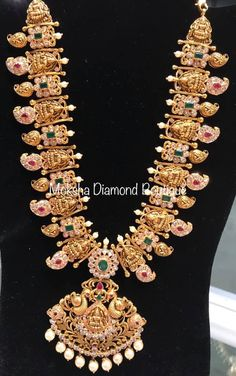 Stunning gold necklace with Lakshmi ji motifs. Necklace with mango hangings. Necklace studded with rubies and emeralds. Necklace with dancing peacock design pendant. Jewelry Design Earrings, Gold Earrings Designs, Gold Jewellery Design, Necklace Designs, Designer Jewellery, Necklace Ideas, Pendant Jewelry, Gold Temple Jewellery, Gold Wedding Jewelry