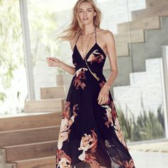 Resplendent blooms energize the black background of this flowy halter dress, accented by fluttery tassels. Thanks to its high-low hem, this design promises to flaunt your legs (and your most-treasured) espadrilles or wedges.