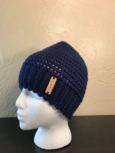 Crochet beanie with a hole in the top so your ponytail or bun can stick out. Its perfect for sports or for those days you want to throw your hair up and still stay warm! Color: navy blue Size: womens Fits head circumference of 23 inches Ready to ship! I have other colors available in my shop. https:// crochetedbycari.etsy.com Handmade by me in my smoke free and pet free home.