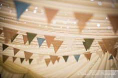 Twinkling fairy lights glistening in the wedding marquee at Wilkswood in Dorset. The pretty vintage bunting adds a rustic charm to the wedding decor.