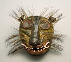 "Jaguar mask. Mexican. 19th century. Glass, painted wood, animal teeth, and boar bristle, 13 x 12 x 7 1/2"" (33 x 30.5 x 19.1 cm). San Antonio Museum of Art."