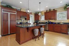 Dark cabinets in open kitchen, fridge has cabinet fronts, island, dark countertops.