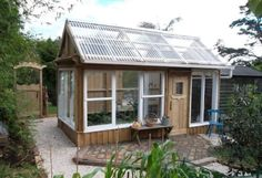 greenhouse from old windows, also tells how u can make a greenhouse from plastic bottles!
