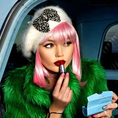 woman wearing fuzzy beret with pink bob and green fuzzy coat applying lipstick.