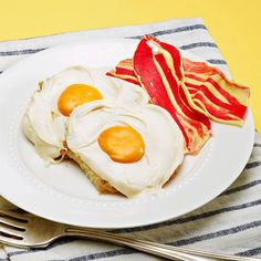 """Trick your family with a surprisingly sweet start to their day. These eggs with a mini marshmallow """"yolk"""" center and taffy bacon are made from cupcakes!"""