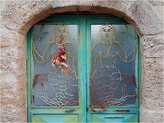 new window in an old Rhodes building. Mermaid motif with flowers. by John Laprairie ©