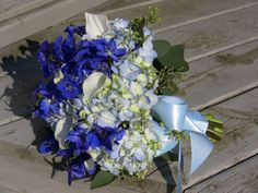 Pretty, classic but with a twist. Hydrangea, delphinium, callas and naked seeded eucalyptus with a satiny bow.