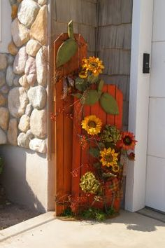 Could make these out of left over fence planks, a couple of 2x4's, feaux flowers, some orange paint and ribbon - too easy. Oh yeah, make free hand drawn leaves and stem on plywood.