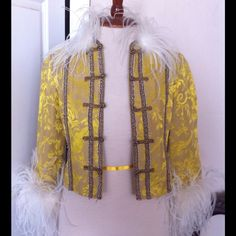 "Gold Brocade Marabou Trim Glam Jacket Truly unique! This was worn in an indie film I worked on about 5 or 6 years ago (I used to do wardrobe for TV and film). It's been sitting unworn in my closet ever since. Fully lined gold brocade with small bead work down the front. Frog toggle closure. White marabou trim at collar and cuffs. By Parameter. Purchased at Anthropologie. Size 4. 16"" from armpit to armpit. 18"" long. Rocker chic with jeans and a tank or glamorous over a simple dress…"