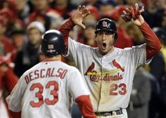 St. Louis Cardinals' David Freese, right, reacts as he and Daniel Descalso score on a single by Pete Kozma in the ninth inning of Game 5 of the National League division baseball series against the Washington Nationals early Saturday, Oct 13, 2012, in Washington.