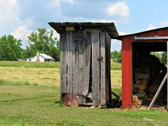 This old outhouse is being used as a woodshed next to the woodshed