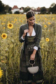 Nina Schwichtenberg trägt ihr Wiesn Outfit von Ludwig & Therese. Zu ihrem khakifarbenen Dirndl und weißer Spitzenbluse kombiniert sie eine dunkelgrüne Stickjacke und ein traditionelles Vintage Charivari. Tasche: Chloé Nile Bag. Mehr auf www.fashiioncarpet.com